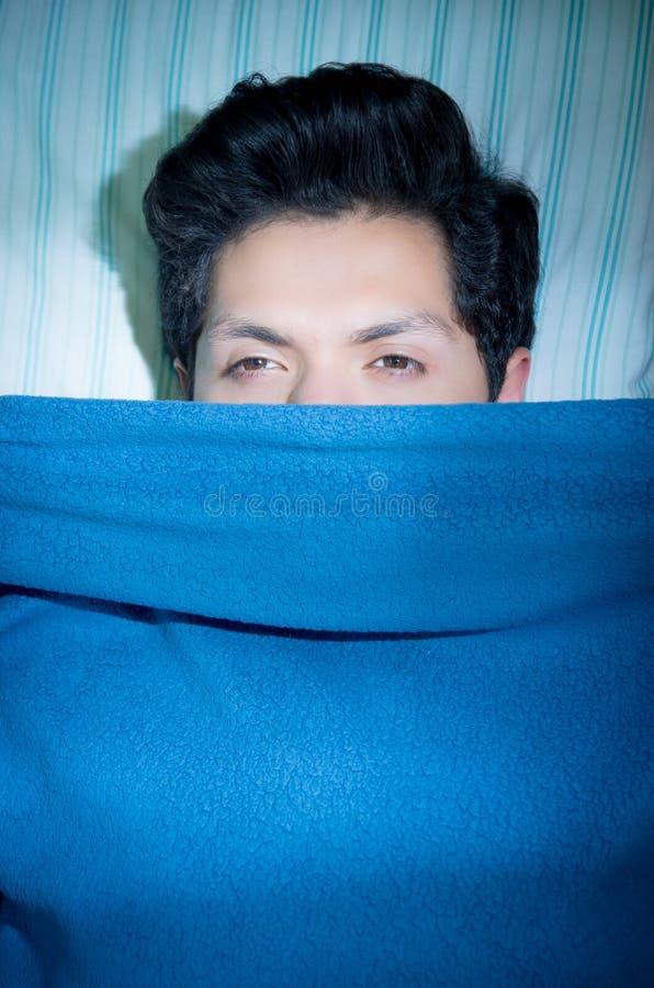 Fermez-vous d'un jeune homme beau dans le lit avec l'insomnie et le trouble du sommeil de souffrance ouverts par yeux pensant au  images libres de droits