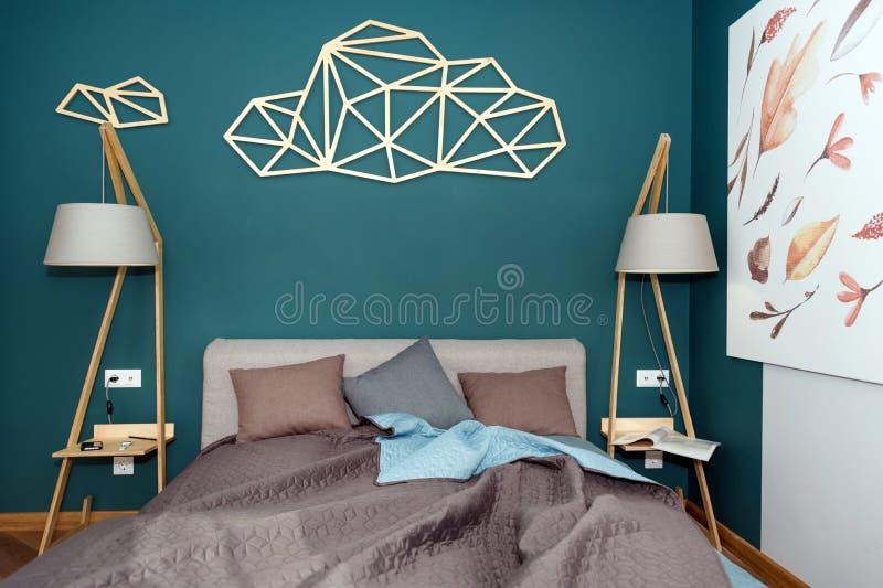 Fermez-vous d'un lit avec les oreillers color?s, le couvre-lit et une lampe confortable Magazine sur la table, ?galisant la lectu photographie stock libre de droits