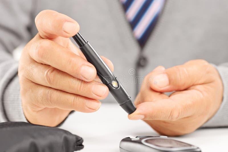 Fermez-vous d'un niveau de mesure mûr de sucre dans le sang utilisant le glucom photographie stock libre de droits
