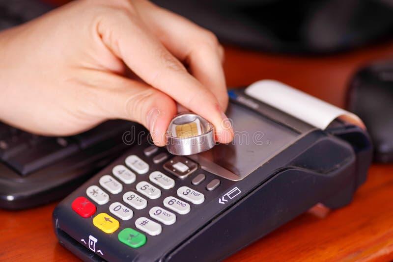 Fermez-vous d'un paiement moderne avec la nouvelle technologie des paiements utilisant un anneau futé avec la puce, achetez et ve photos stock