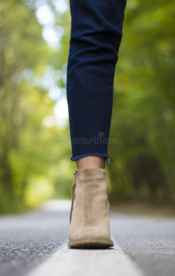 Fermez-vous d'un pied et d'une botte élégante - fond de forêt photos stock