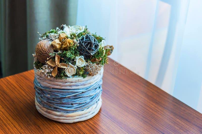 Fermez-vous d'un pot de fleur en osier avec la disposition de fleurs sèche au-dessus d'une table en bois par la fenêtre photo stock