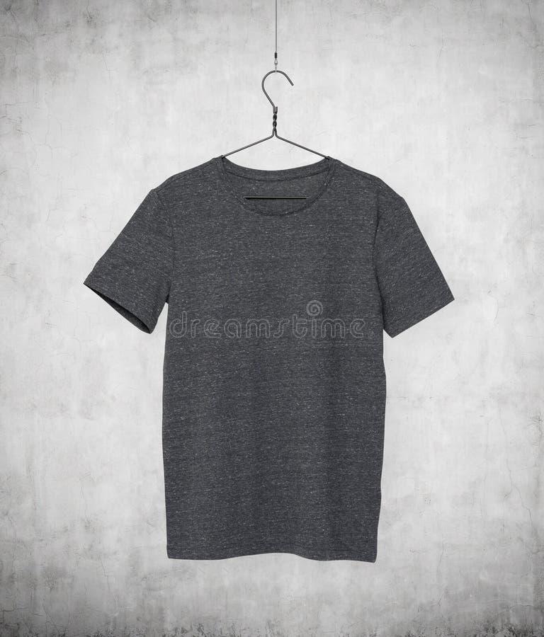 Fermez-vous d'un T-shirt gris sur le cintre de tissu photo libre de droits