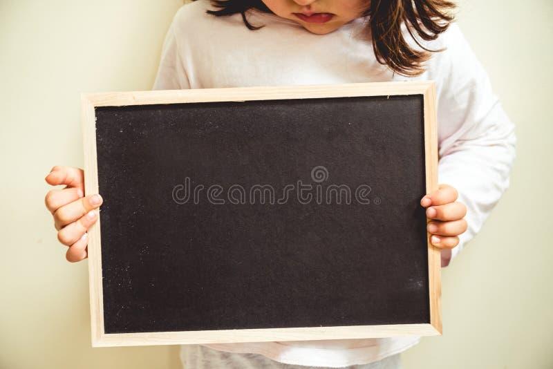 Fermez-vous d'un tableau vide tenu par un enfant qui boude photos libres de droits