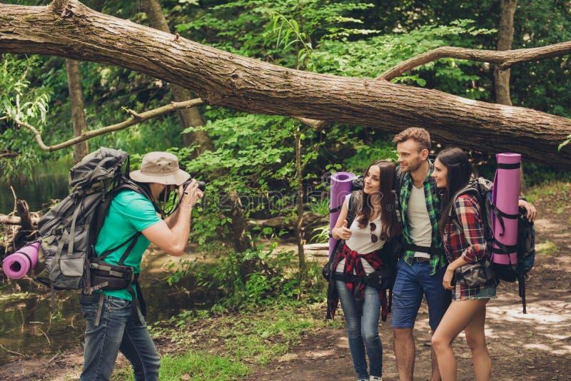 Fermez-vous d'un type tirant un portrait de ses trois amis dans le bois gentil d'été Ils sont des randonneurs, marchant et sélect photos libres de droits