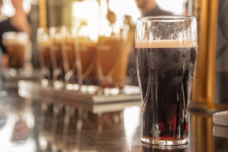 Fermez-vous d'un verre de bière vaillante dans une barre images libres de droits
