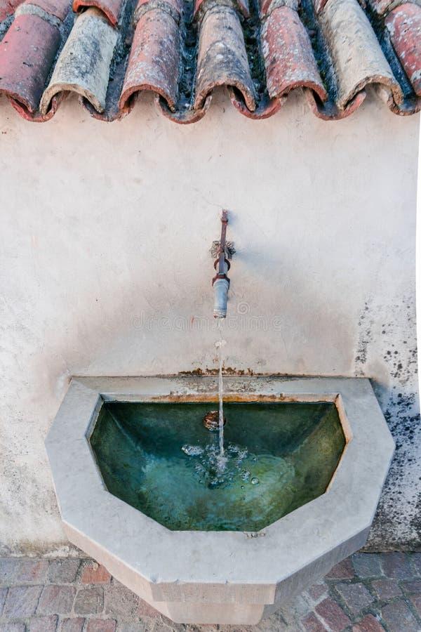 Fermez-vous d'un vieux et rustique poste d'eau potable dans un village européen idyllique photographie stock