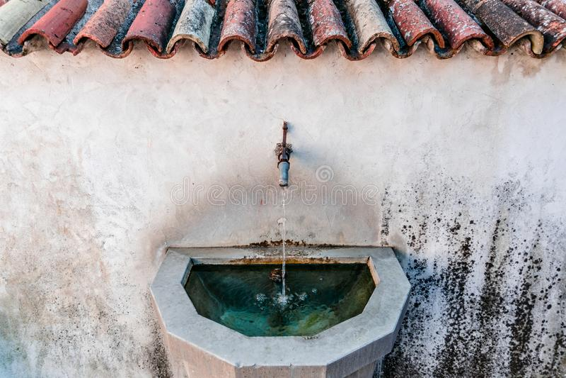 Fermez-vous d'un vieux et rustique poste d'eau potable dans un village européen idyllique photo stock