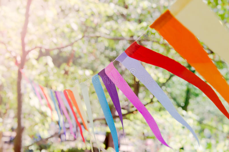 Fermez-vous d'une bannière colorée de partie attachée entre les arbres en parc à un événement de célébration d'air ouvert images libres de droits