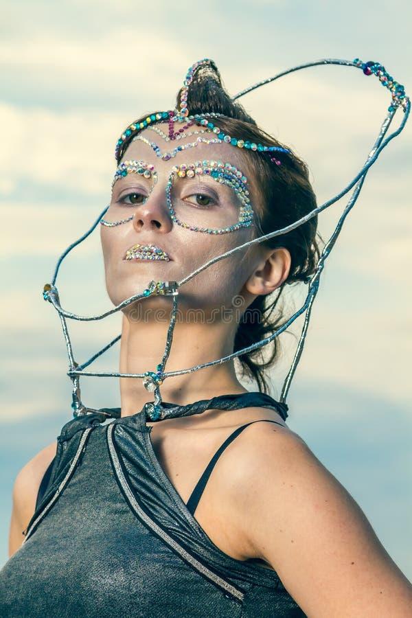 Fermez-vous d'une belle femme avec des cristaux collés sur son visage photographie stock