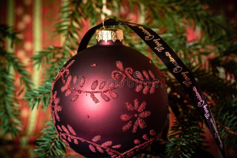 Fermez-vous d'une boule rouge d'arbre de Noël avec des ornements photographie stock