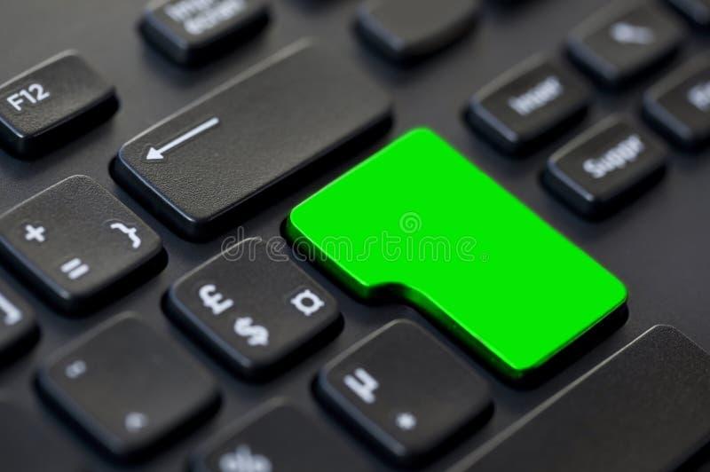 Fermez-vous d'une clé de retour vide verte sur un ordinateur noir photographie stock