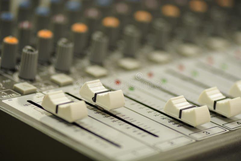 Fermez-vous d'une console de mélange avec des glisseurs et des boutons photographie stock libre de droits