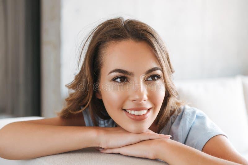 Fermez-vous d'une détente de sourire de jeune femme photos libres de droits