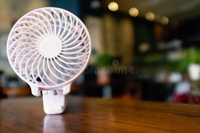 Fermez-vous d'une fan à piles portative, plié sur une table en bois La partie intérieure tourne avec la tache floue de mouvement photographie stock libre de droits