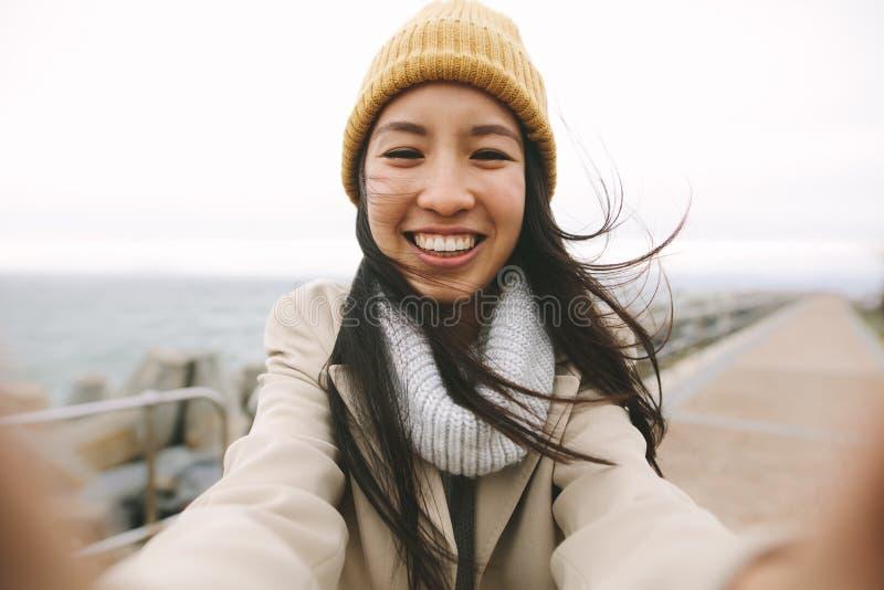 Fermez-vous d'une femme de sourire dans la position d'usage d'hiver près de la mer images libres de droits