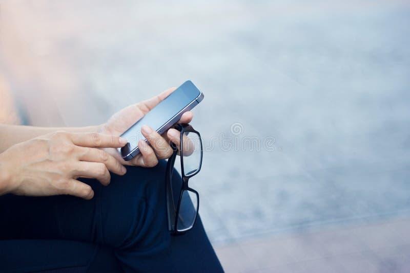 Fermez-vous d'une femme employant le téléphone intelligent mobile extérieur et les verres photographie stock libre de droits