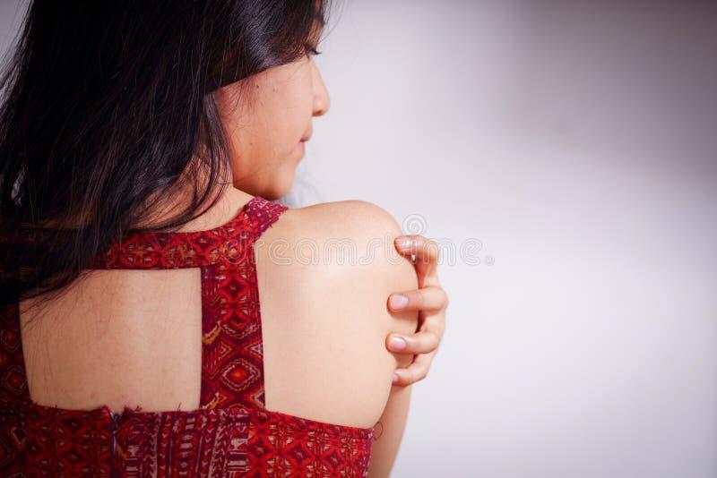 Fermez-vous d'une jeune femme rayant son épaule avec sa main après avoir été violé et souffrant la violence sexuelle, dans un bla images libres de droits