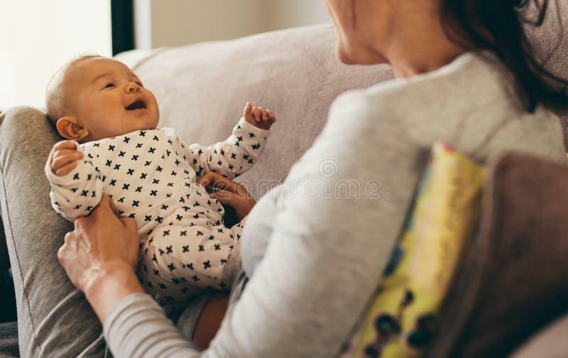Fermez-vous d'une mère s'asseyant avec son bébé à la maison image libre de droits