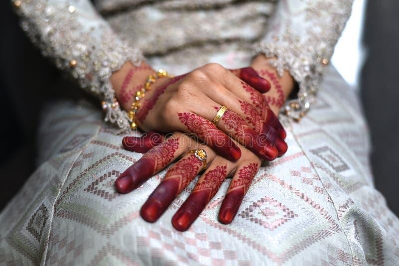 Fermez-vous d'une main malaise de jeune mariée avec des anneaux de tatouage et d'or de henné son jour du mariage images libres de droits