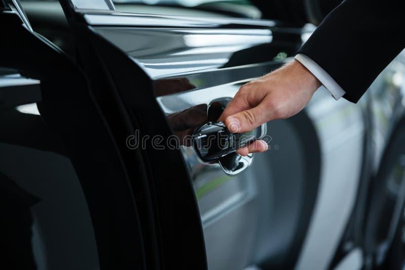 Fermez-vous d'une main masculine fermant une portière de voiture photo stock