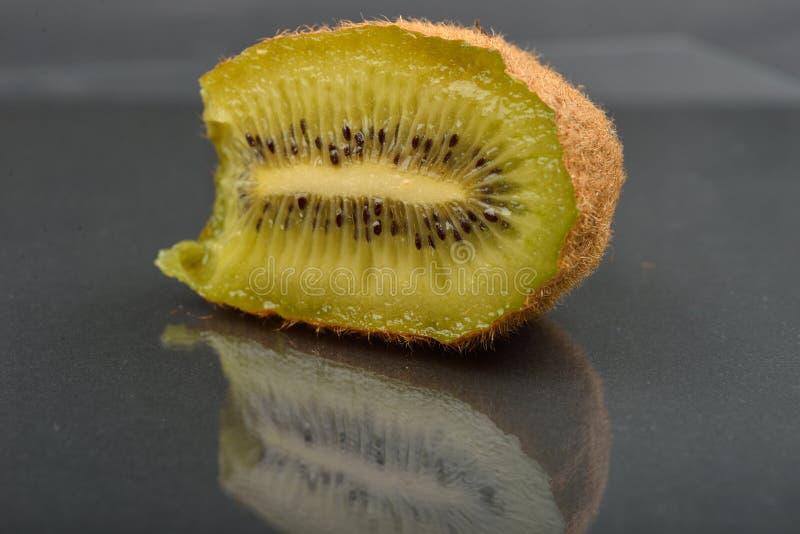Fermez-vous d'une moitié de kiwi avec laquelle a été mordu avec des dents wize image stock