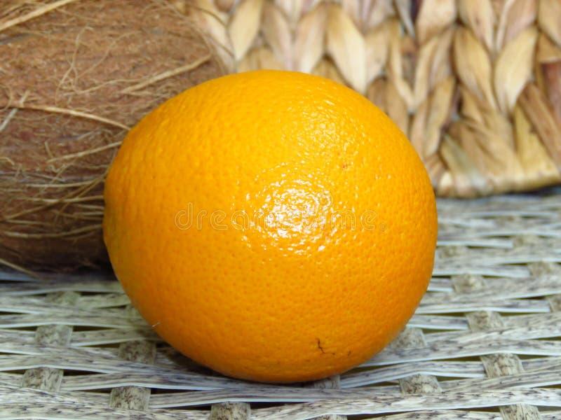 Fermez-vous d'une orange sur un fond tissé fait main de travaux de bambou de canne de noix de coco et de rotin photographie stock libre de droits