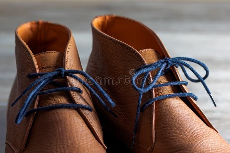 Fermez-vous d'une paire de bottes brunes de robe de nubuck avec les dentelles bleues image stock