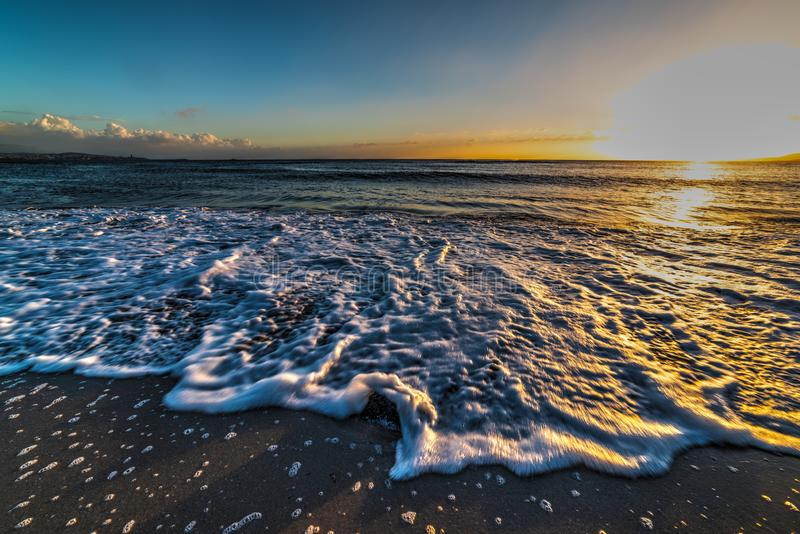 Fermez-vous d'une petite vague sur les lais au coucher du soleil photo stock