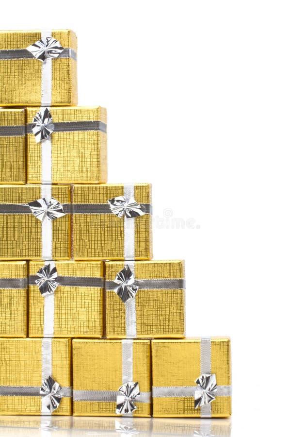 Fermez-vous d'une pile des cadeaux d'or sur le blanc photos stock