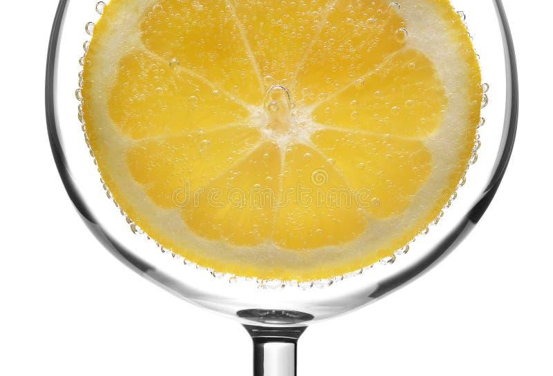 Fermez-vous d'une tranche de citron dans un verre de l'eau carbonatée photos libres de droits