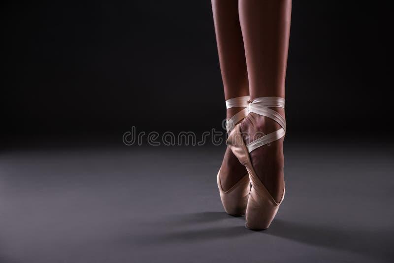 Fermez-vous de des pieds du ` s de danseur classique au-dessus du gris photos stock