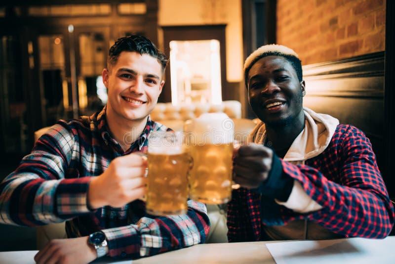 Fermez-vous de deux amis heureux d'un homme buvant de la bière à la barre ou au bar photographie stock