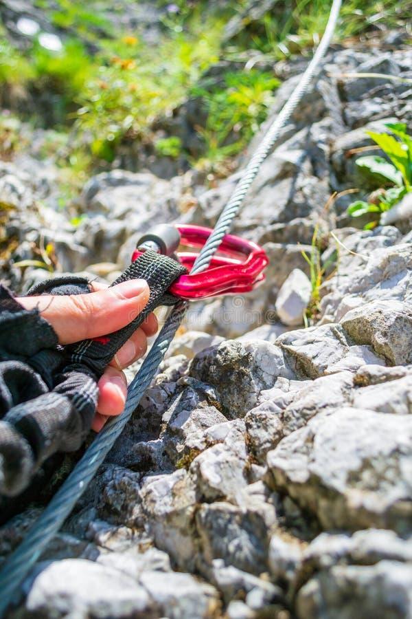 Fermez-vous de deux carabiners de verrouillage rouges étant soulevés le long d'un fil d'acier par une main masculine avec des g photo stock