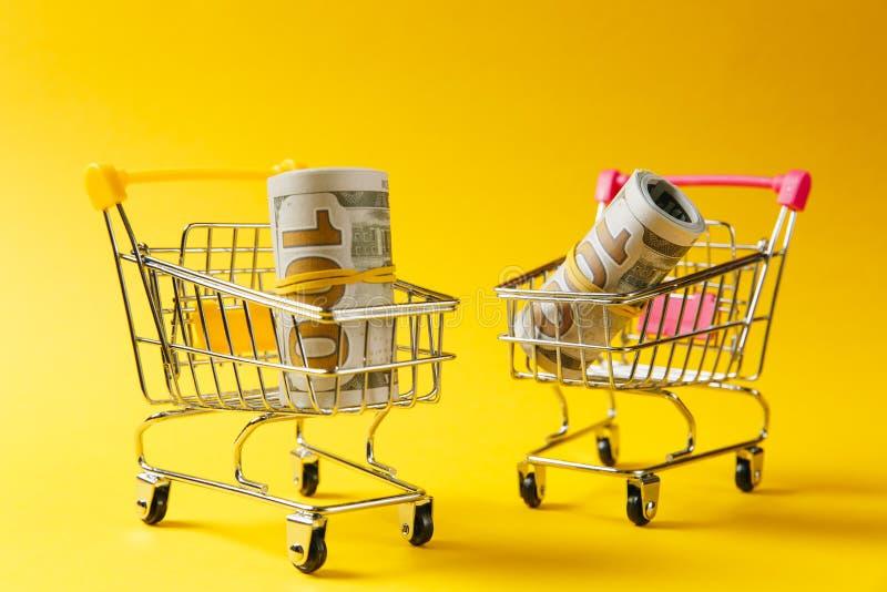 Fermez-vous de deux chariots de poussée d'épicerie de supermarché pour faire des emplettes avec la poignée jaune et rose avec des photographie stock