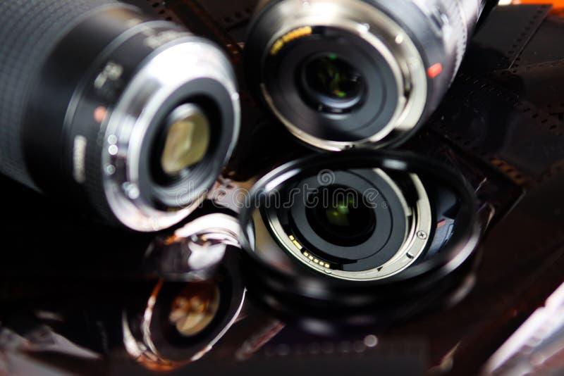 Fermez-vous de deux objectifs de caméra avec le filtre circulaire d'isolement sur des bandes de film négatif images stock