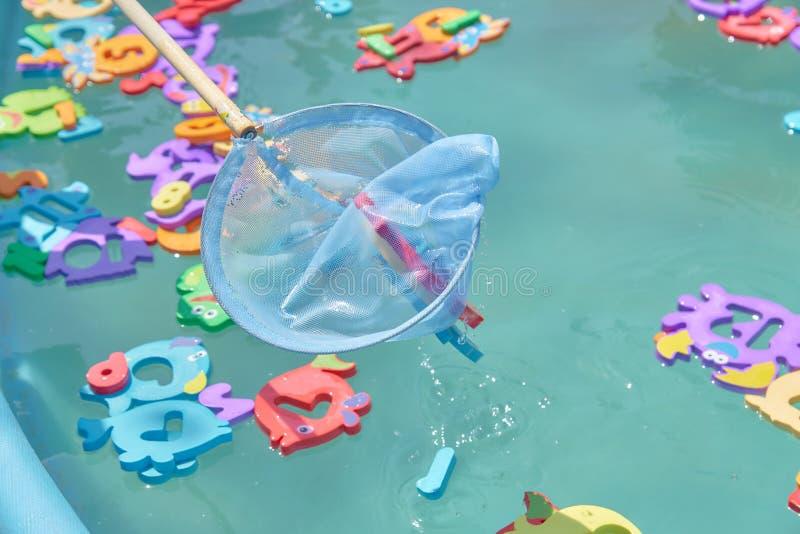 Fermez-vous de flotter les figures animales marines colorées dans la piscine pour attraper un filet divertissement du ` s d'enfan photo stock