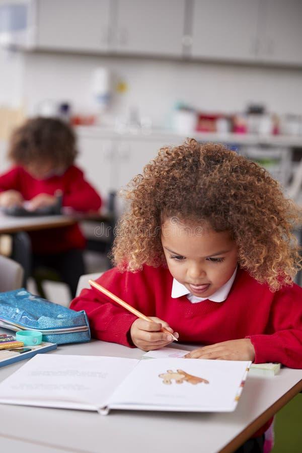 Fermez-vous de l'écolière de métis s'asseyant au bureau dans un dessin de salle de classe d'école infantile, verticale images stock