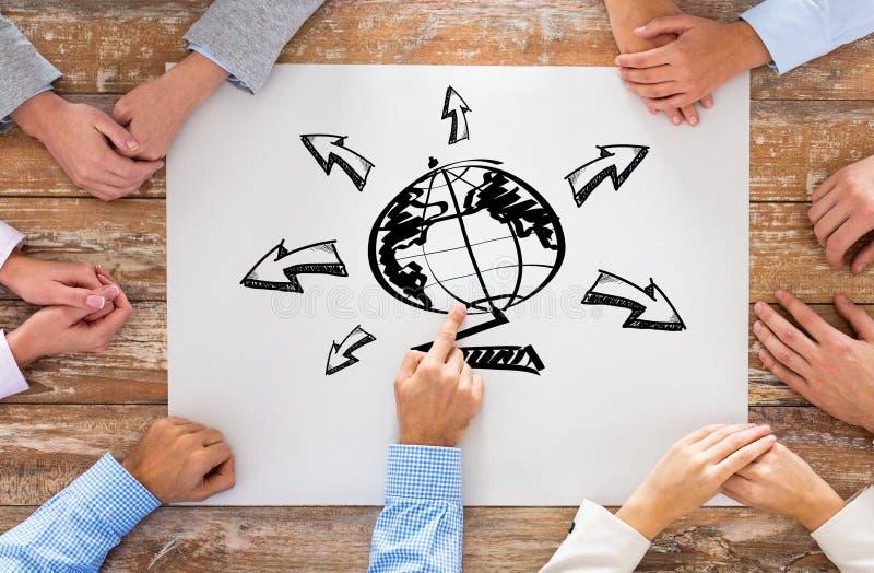 Fermez-vous de l'équipe d'affaires avec le dessin de globe image stock