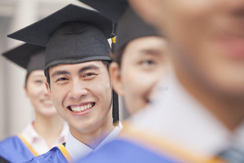 Fermez-vous de l'étudiant de troisième cycle masculin Standing dans une rangée des diplômés photographie stock