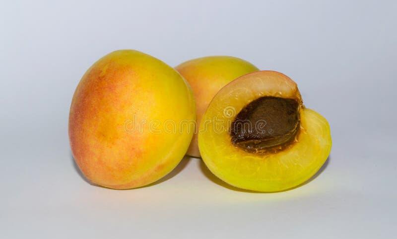 Fermez-vous de l'abricot trois organique frais sur un backgrpund blanc photo stock