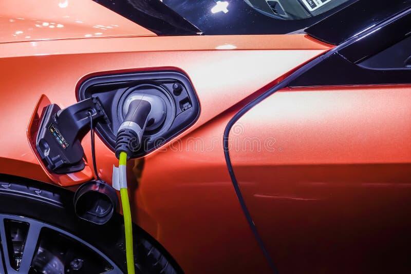 Fermez-vous de l'alimentation d'énergie branchée à une voiture électrique étant chargée images stock