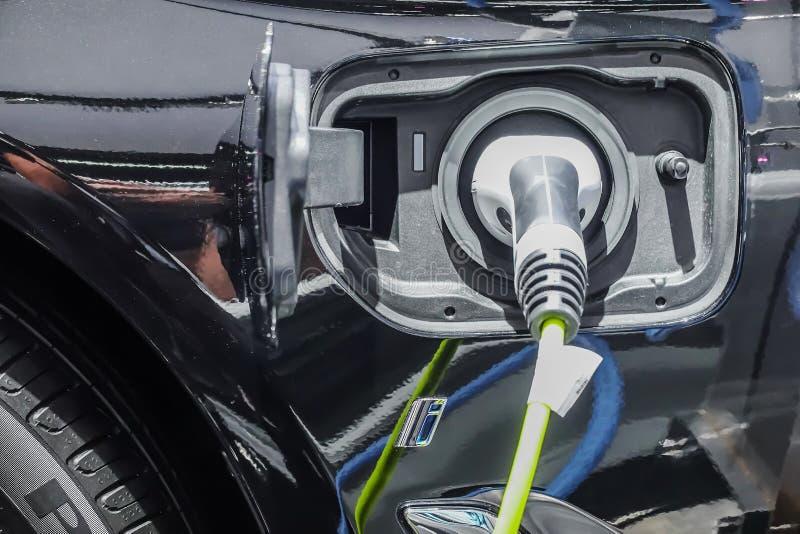 Fermez-vous de l'alimentation d'énergie branchée à une voiture électrique étant chargée photographie stock libre de droits