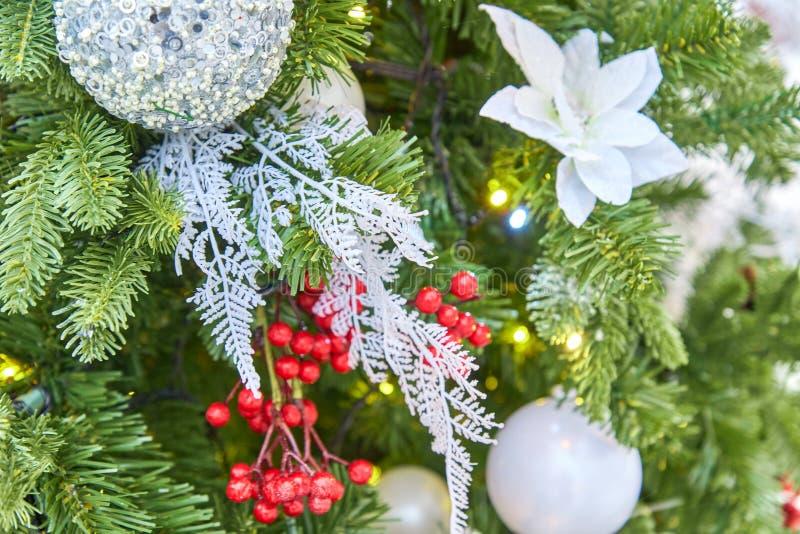 Fermez-vous de l'arbre de Noël décoré des boules et de la guirlande de scintillement argentées avec des lumières dessus Fond de f photos libres de droits