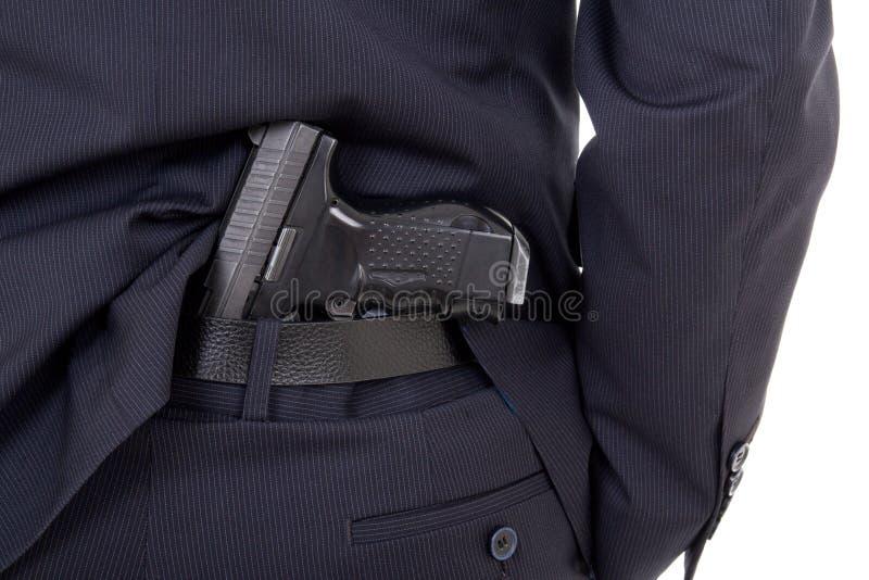 Fermez-vous de l'arme à feu dans le pantalon de costume d'isolement sur le blanc image stock