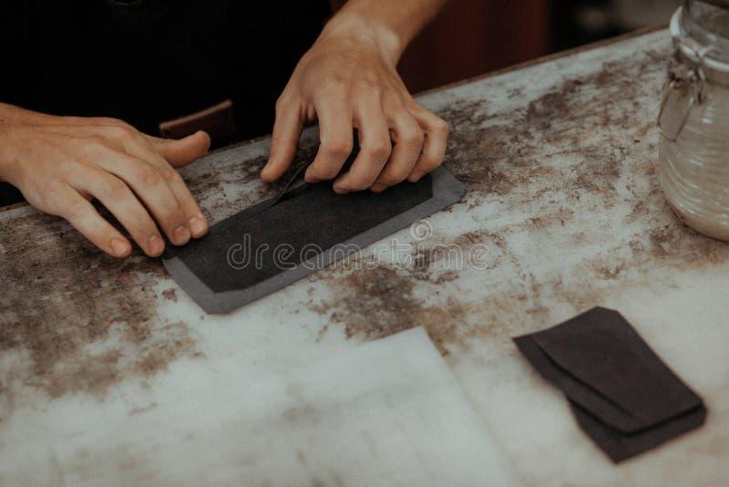Fermez-vous de l'artisan en cuir travaillant avec le cuir naturel Maître fait main au travail dans l'atelier local Concept fait m images libres de droits