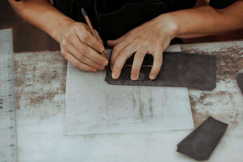 Fermez-vous de l'artisan en cuir travaillant avec le cuir naturel utilisant des outils Maître fait main au travail dans l'atelier photographie stock