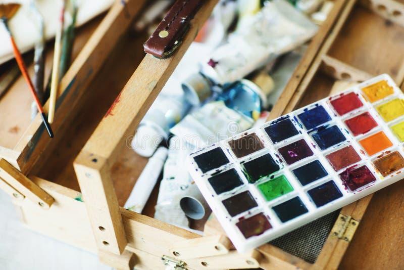 Fermez-vous de l'artiste en bois de valise avec la peinture d'aquarelle, les brosses et les outils artistiques Concept d'art photos stock