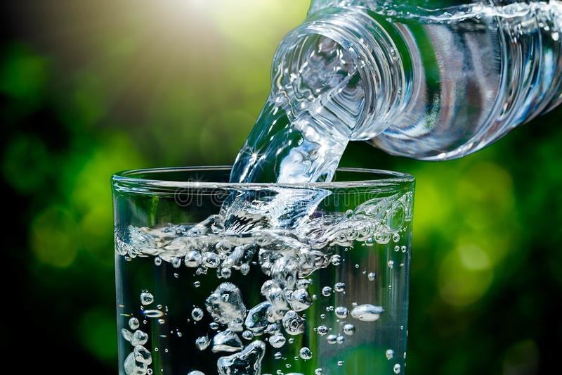 Fermez-vous de l'eau découlant de la bouteille d'eau potable dans le verre sur le fond vert brouillé de bokeh de nature avec la l photographie stock