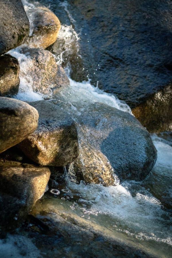 Fermez-vous de l'eau fonctionnant au-dessus des roches photo stock